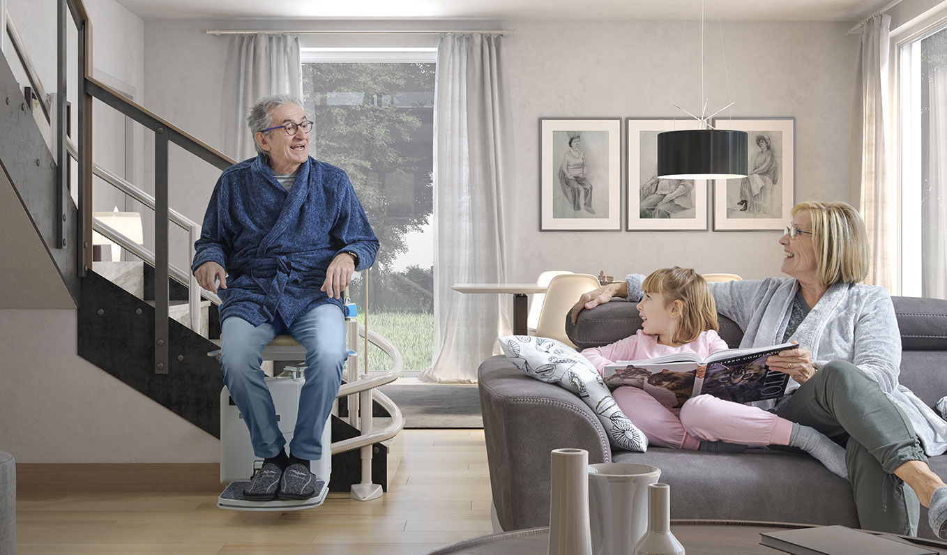 Man sitting on stairlift with wife and grandchild