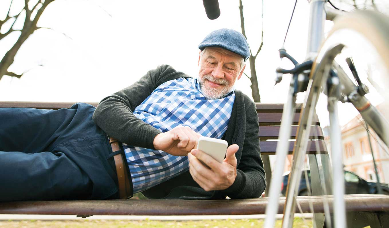 Senior man sitting on bench using smartphone