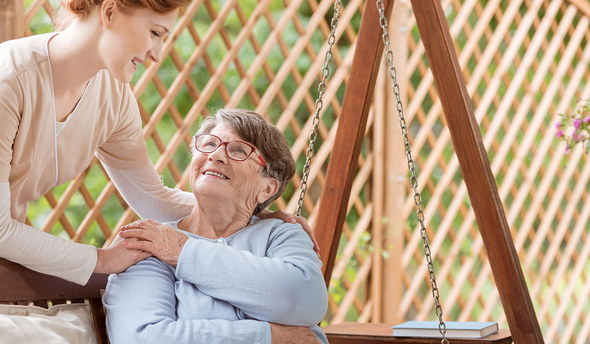 elderly woman with caregiver outside